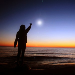 Silhouette of child on beach at dusk/dawn with hand outstretched toward a rising/setting sun/star