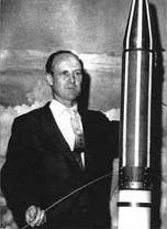 A young will pickering standing next to  model rocket